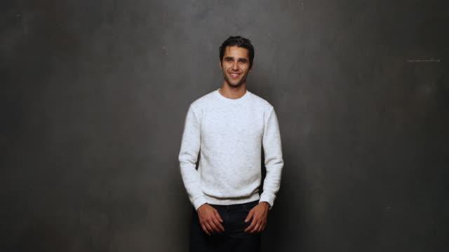vidéos et rushes de portrait of young man smiling at camera - jeans texture