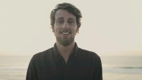 vidéos et rushes de portrait of young man, smiling into camera at sunset on dune on a beach at atlantic ocean in the south of france - jeunes hommes