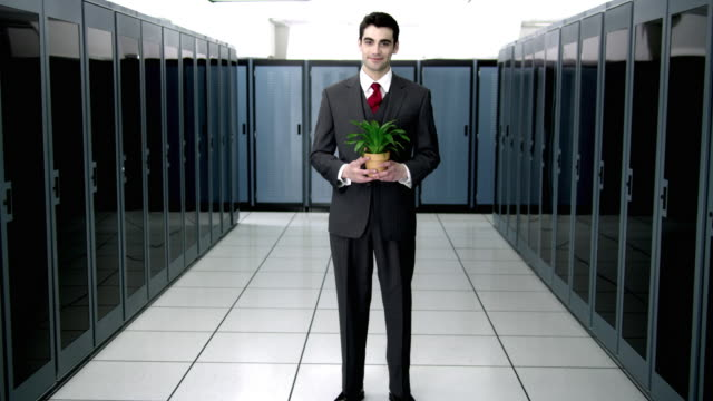 ws ds ms portrait of young man standing in server room, holding potted plant - see other clips from this shoot 1480 stock videos and b-roll footage