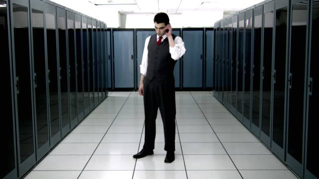 ws cu portrait of young man talking on mobile phone in server room - see other clips from this shoot 1480 stock videos and b-roll footage