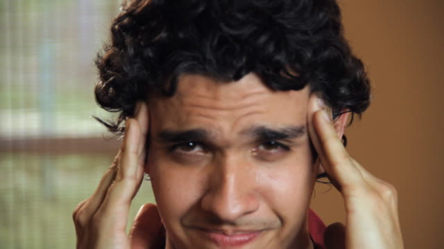 cu portrait of young man with headache pressing temples with fingers / madison, florida, usa - forehead stock videos and b-roll footage