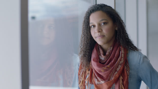 vídeos y material grabado en eventos de stock de slo mo. portrait of young mixed-race woman standing next to airport terminal window. - pasajero