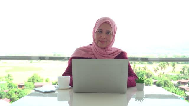 vidéos et rushes de portrait de jeunes femmes d'affaires musulmanes en tissu religieux en hiver à l'aide d'un ordinateur portable et souriant pendant le travail sur le balcon d'un hôtel, appartement au milieu de la scène verte, vue non urbaine - non urban scene