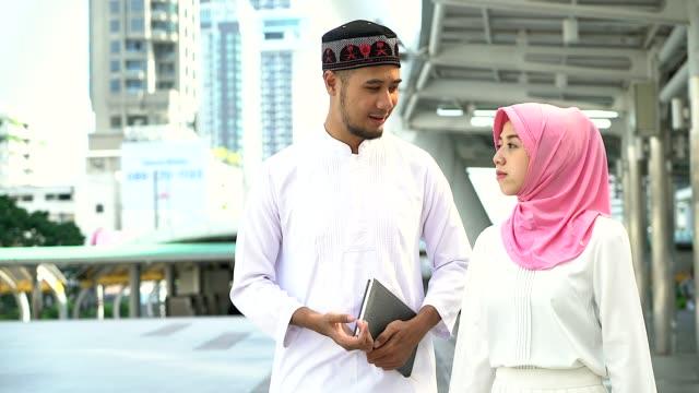 vidéos et rushes de portrait de jeune homme musulman et la femme debout dans la ville, portrait du concept de population musulmane. - vêtement religieux