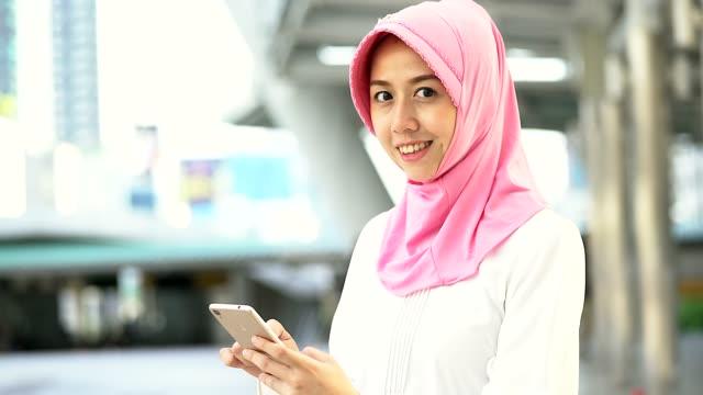 Retrato de jovens mulheres muçulmanas jogando móvel na cidade, retrato do conceito do povo muçulmano.