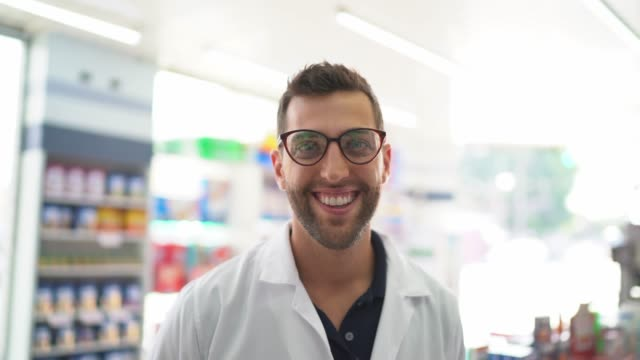 portrait of young pharmacist standing in a drugstore - males stock videos & royalty-free footage