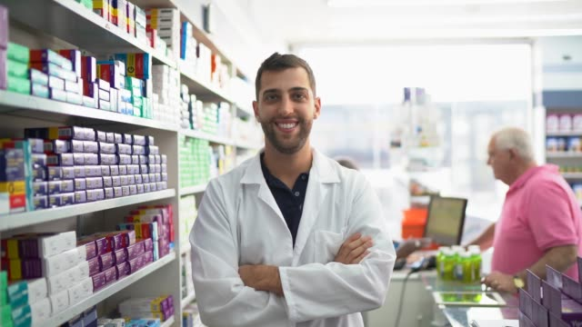 portrait of young pharmacist standing with arms crossed in a drugstore - males stock videos & royalty-free footage