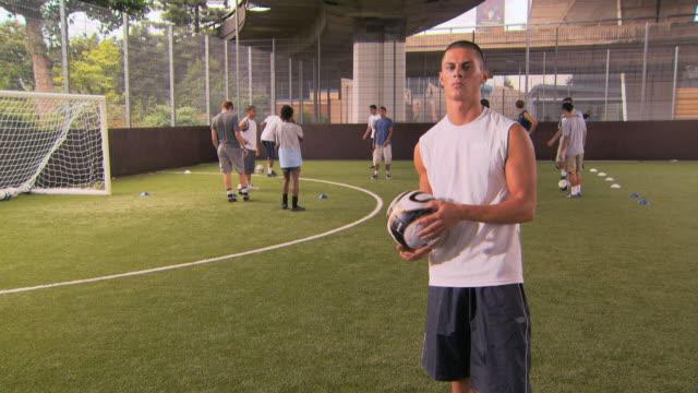 vídeos de stock, filmes e b-roll de ms portrait of young player, others training in background, london, uk - segurando