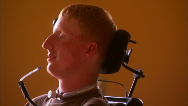 cu portrait of young quadriplegic man with head brace and wheelchair steering mouthpiece / halifax, nova scotia - paralysis stock videos & royalty-free footage