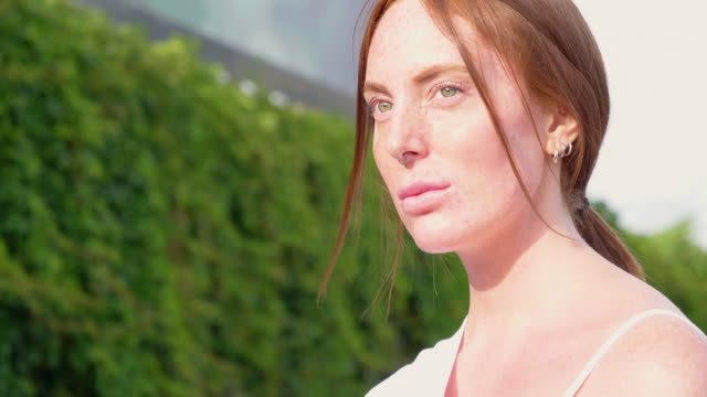 portrait of young redhead woman with nose ring outdoors - nose piercing stock videos & royalty-free footage