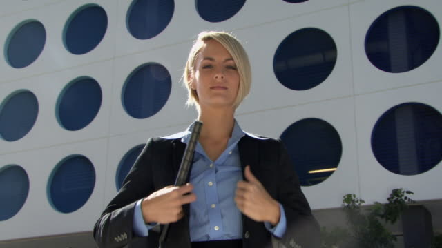 MS LA Portrait of young reporter holding microphone in front of modern office building / Miami, Florida, USA