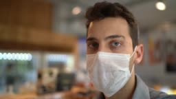 Portrait of young small business man owner with face mask