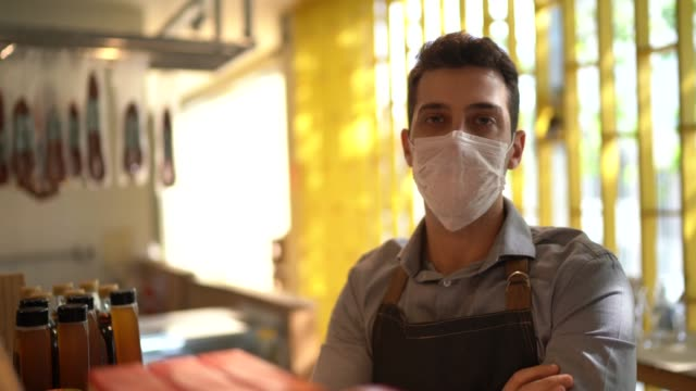 vídeos de stock e filmes b-roll de portrait of young small business man owner with face mask - trabalho no comércio