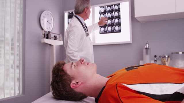 vídeos de stock, filmes e b-roll de portrait of young sports athlete lying down while doctor reviews xrays - physical injury