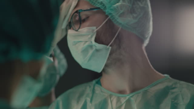 portrait of young surgeon performing surgical operation - surgeon stock videos & royalty-free footage