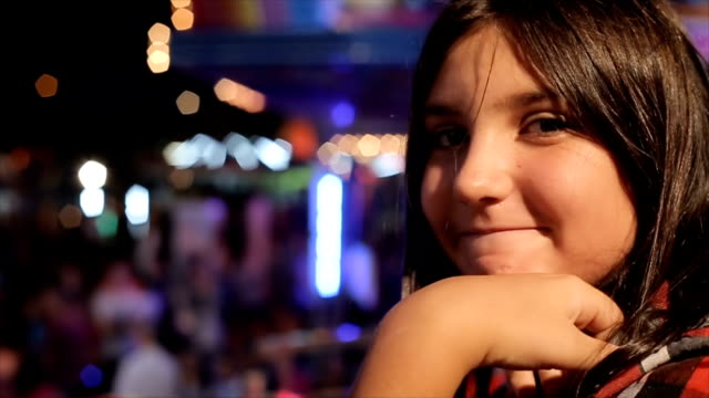 portrait of young teenage girl in amusement park in the night - fairground ride stock videos & royalty-free footage