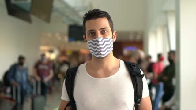 portrait of young traveller man wearing face mask on airport - rucksack stock videos & royalty-free footage