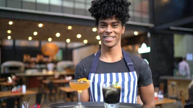 portrait of young waiter holding a tray with a few drinks - cocktail stock videos & royalty-free footage