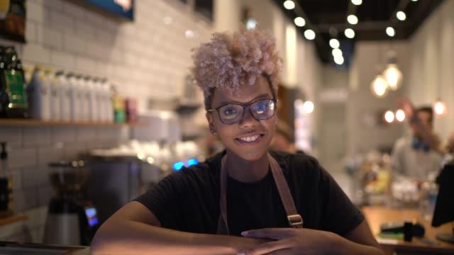 vídeos de stock e filmes b-roll de portrait of young waitress working in coffee shop - empregada de mesa