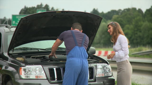 Portrait of young woman and auto mechanic shaking hands by car next to highway, Ljubljana, Slovenia