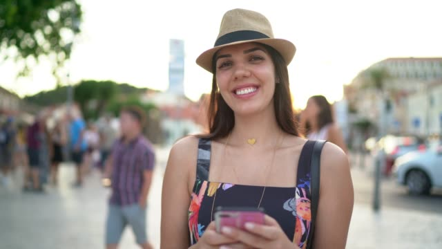 vídeos de stock e filmes b-roll de portrait of young woman and holding a mobile phone in dubrovnik, croatia - mobile