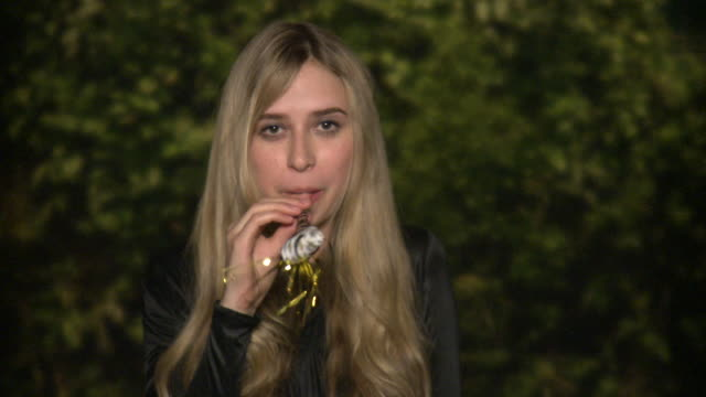 CU Portrait of young woman blowing party whistle outdoors, New York City, New York, USA