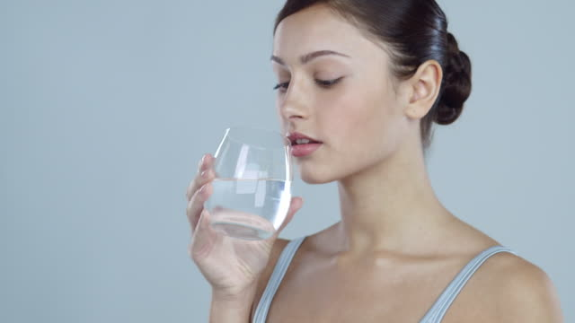 Portrait of young woman drinking a glass of water looking away from camera