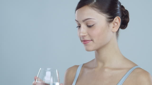 Portrait of young woman drinking a glass of water