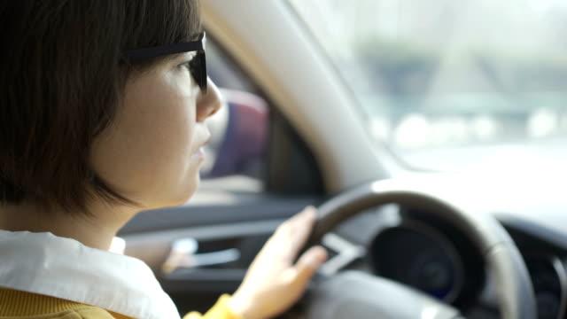 vidéos et rushes de verticale de la jeune voiture de conduite de femme - lunette soleil