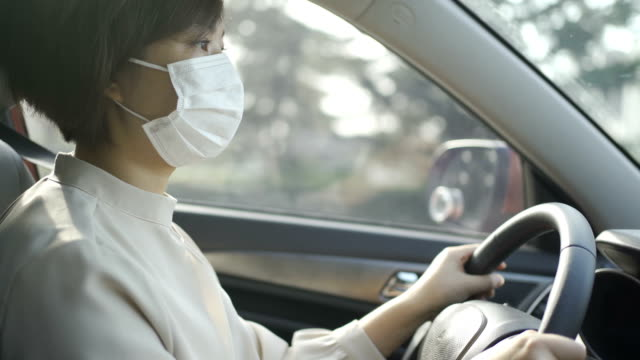 portrait of young woman driving car with mask - safety stock videos & royalty-free footage