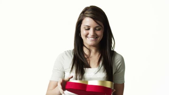 vídeos de stock, filmes e b-roll de ms portrait of young woman eating candy against white background / orem, utah, usa - orem utah