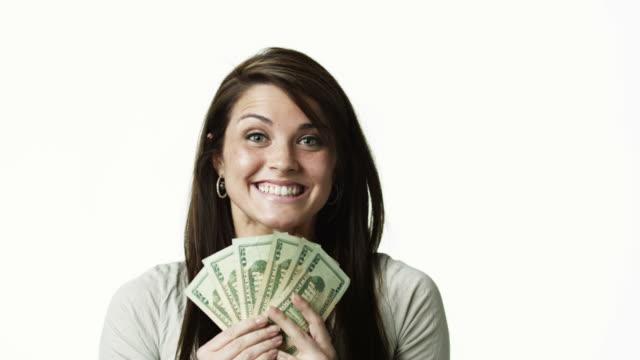 stockvideo's en b-roll-footage met ms portrait of young woman holding banknotes against white background / orem, utah, usa - orem utah