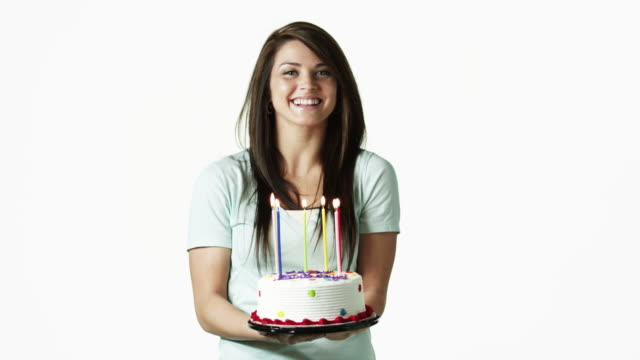 ms portrait of young woman holding birthday cake against white background / orem, utah, usa - orem utah stock videos & royalty-free footage