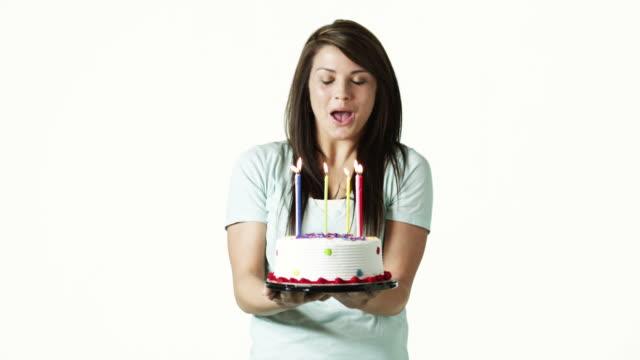 MS Portrait of young woman holding birthday cake against white background / Orem, Utah, USA