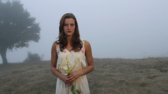 vídeos de stock, filmes e b-roll de ms portrait of young woman holding bouquet of yellow wildflowers / big sur, california, usa - bouquet