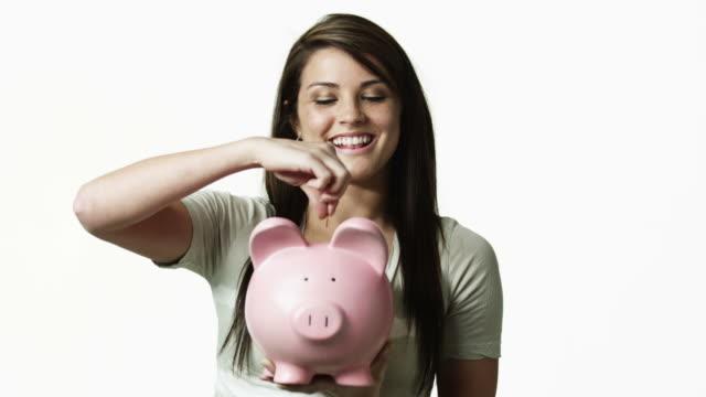 vídeos de stock, filmes e b-roll de ms portrait of young woman holding piggy bank against white background / orem, utah, usa - orem utah