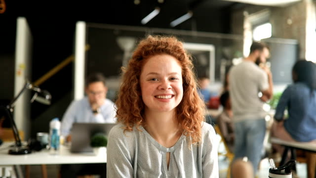 portrait of young woman in a busy modern workplace - redhead stock videos & royalty-free footage