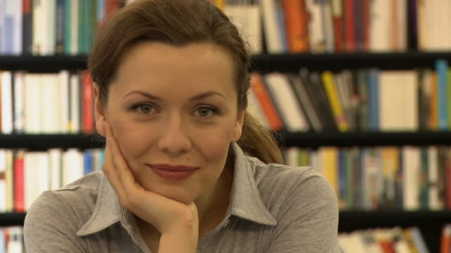 cu, portrait of young woman in bookshop, berlin, germany - hand am kinn stock-videos und b-roll-filmmaterial