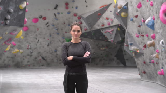ms portrait of young woman in front of a climbing wall - arms crossed stock videos & royalty-free footage