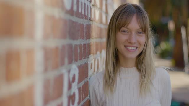 vídeos de stock e filmes b-roll de portrait of young woman in front of a wall - fotografia da cabeça