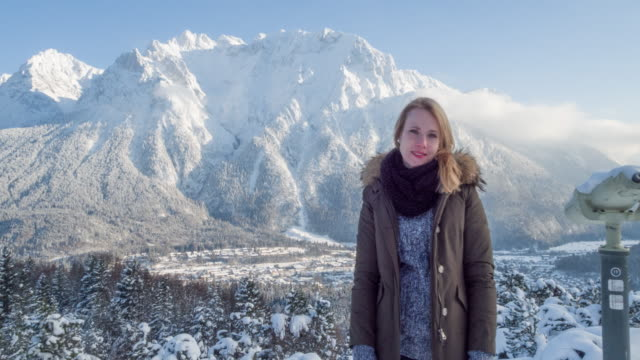 vidéos et rushes de portrait of young woman in front of mountain panorama in winter - zoom out