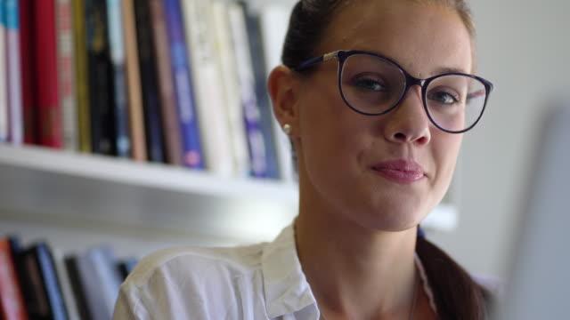 vídeos y material grabado en eventos de stock de retrato de la mujer joven en la biblioteca potting down eyeglasses y mirando a la cámara - gafas