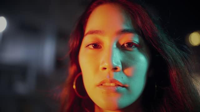 porträt der jungen frau von neonfarbenen lichtern in der stadt in der nacht beleuchtet - leuchtende farbe stock-videos und b-roll-filmmaterial