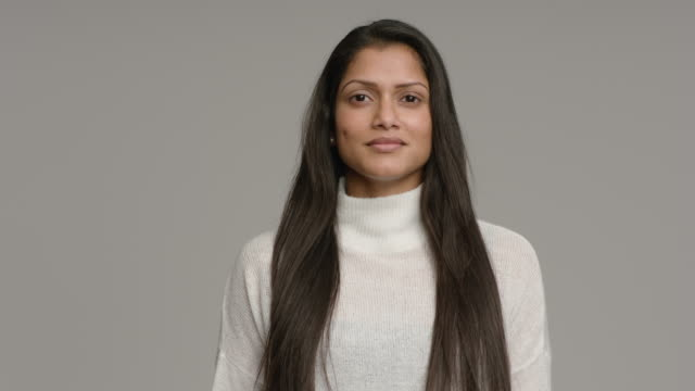 MS Portrait of Young woman on grey background, shot in slow motion