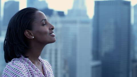 cu portrait of young woman on roof with defocused cityscape in background, chicago, illinois, usa - profile stock videos & royalty-free footage