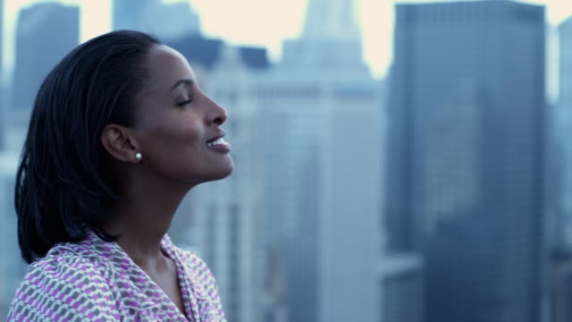 cu portrait of young woman on roof with defocused cityscape in background, chicago, illinois, usa - profile stock-videos und b-roll-filmmaterial
