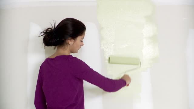 ms, pan, portrait of young woman painting wall with paint roller, plainfield, new jersey, usa - paint roller stock videos & royalty-free footage