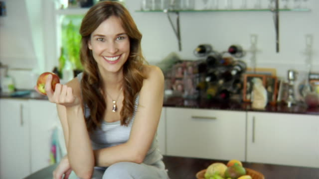 slo mo ms pan portrait of young woman playing with apple in kitchen / london, united kingdom - apfel stock-videos und b-roll-filmmaterial
