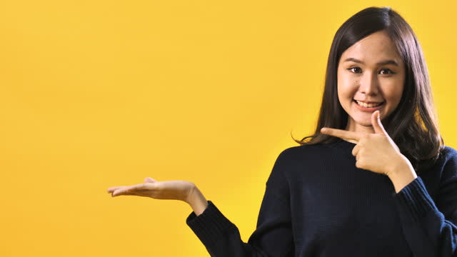 portrait of young woman pointing towards message copy space against a yellow studio background - pointing stock videos & royalty-free footage