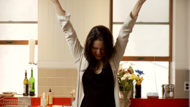 ms portrait of young woman raising arms standing in kitchen, brooklyn, new york city, new york state, usa - punching the air stock videos & royalty-free footage